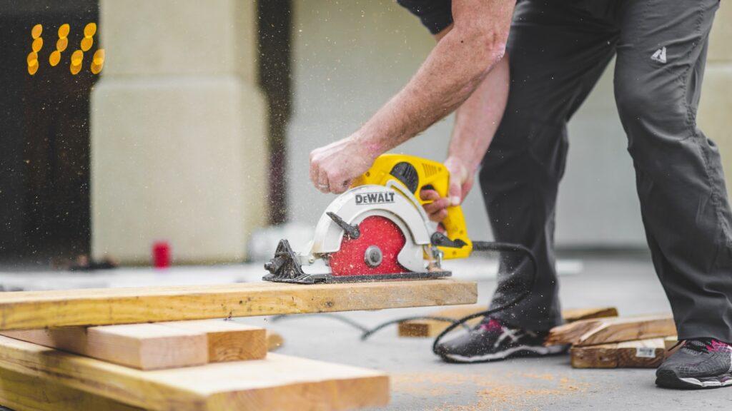 man cutting wood boards with DeWalt power saw
